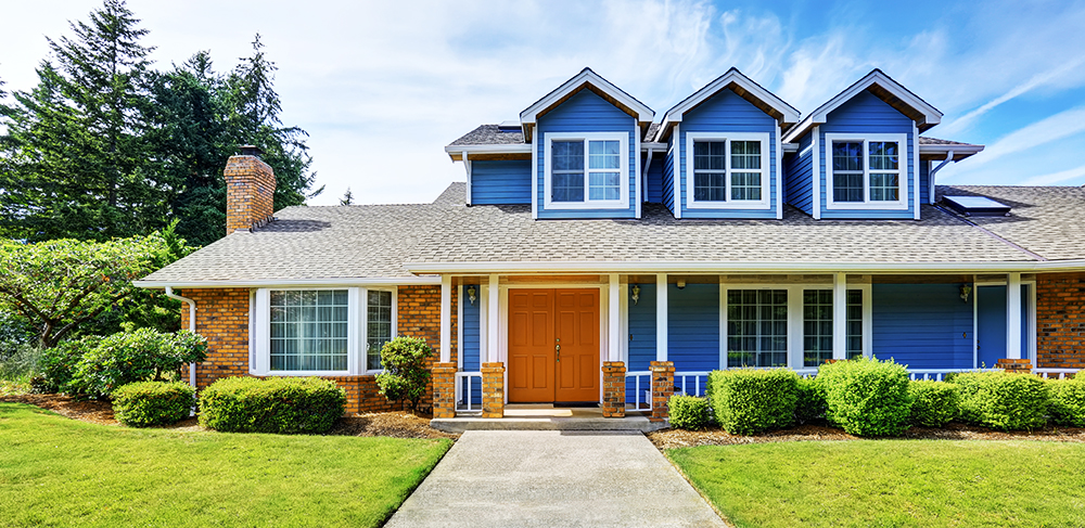 Blue House exterior with an orange door, white trim and a green grass front yard.