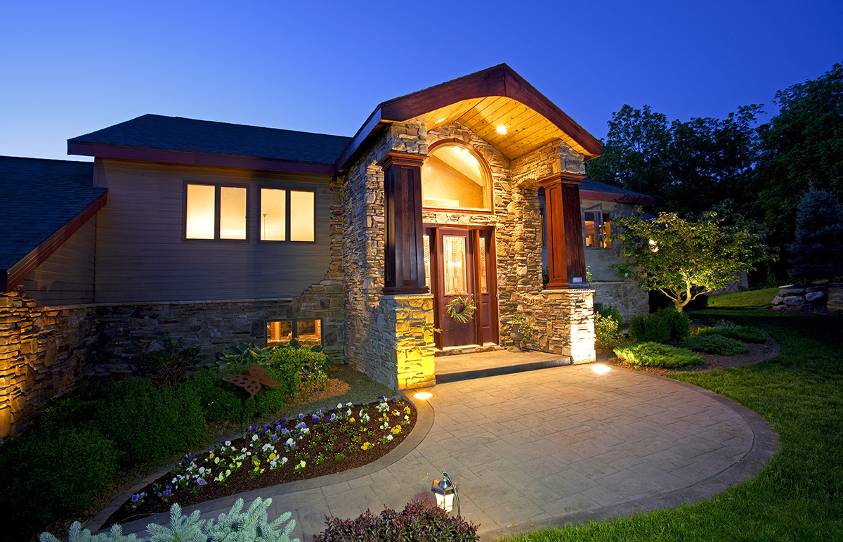 Exterior of a luxury home at dusk with the warm glow of exterior and interior lights.